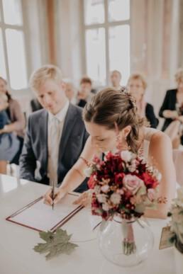 Braut unterschreibt bei Herbsthochzeit in Niederbayern, fotografiert von Martina Feicht Fotografie, Passau