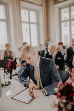 Bräutigam unterzeichnet im Standesamt bei Herbsthochzeit in Niederbayern, fotografiert von Martina Feicht Fotografie, Passau