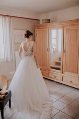 Braut betrachtet sich im Kleid, bei Hochzeit in Freyung, Sommerhochzeit fotografiert von Martina Feicht, für Hochzeiten in Niederbayern und Österreich