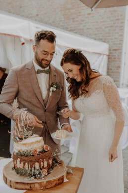 Hochzeitstorte wird angeschnitten vom Brautpaar und mit der Hochzeitsfotografin Martina Feicht Fotografie