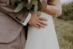 Hände mit Ring berühren die Braut beim Brautpaarhsooting