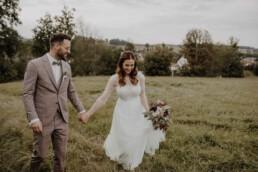 Glücklicher Bräutigam lächelt seine Braut an und Hochzeitsfotografin Martina Feicht fotografiert sie