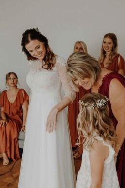 Brautmutter und Braut beim Getting Ready, hier wird das Brautkleid angezogen