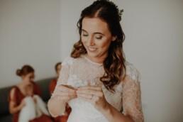 Die wunderschöne Braut legt ihren Schmuck an und wird dabei von Martina Feicht fotografiert