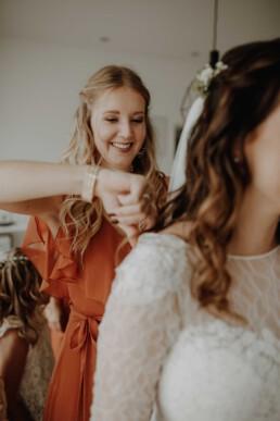 Die Brautjungfer hilft der Braut beim anlegen des Brautkleides am Hochzeitstag