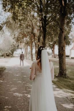 Die Braut kommt zum First Look in ihren weißen Hochzeitskleid und wird gleich zum ersten mal auf ihren Bräutigam treffen