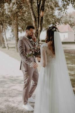 Braut steht hinter Bräutigam und bittet ihn sich umzudrehen in ihrem Hochzeitskleid fotografiert von Martina Feicht