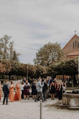 Hochzeitsgäste warten vor der Kirche in Passau auf das Brautpaar und werden von Martina Feicht fotografiert