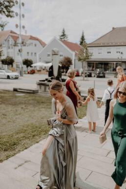 Mit einem eleganten Outfit machen sich die Hochzeitsgäste auf zur Kirche und warten auf das Brautpaar im BMW