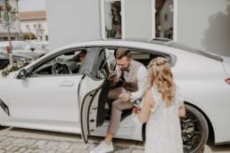 Der Bräutigam steigt aus dem Brautauto BMW aus und nimmt seine Nichte in den Arm