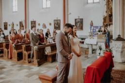 Brautpaar steht am Altar in der Kirche und die Hochzeitszeremonie beginnt gleich in der Nähe von Passau