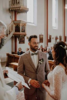 Braut und Bräutigam stehen sich gegenüber bei der kirchlichen Trauung fotografiert von Martina Feicht , Passau