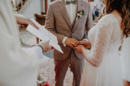 Hände des Brautpaares mit dem Ehering und geben sich das Eheversprechen