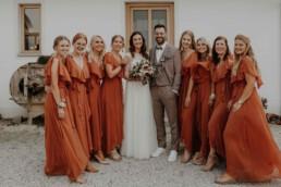 Gruppenbild mit den Brautjungfern und Braut und Bräutigam an der Hochzeitslocation, Martina Feicht Fotografie